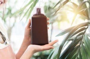 Female hands holding bottle of liquid fertilizer in garden