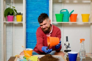Happy man is played with plants. Soil for house plants.