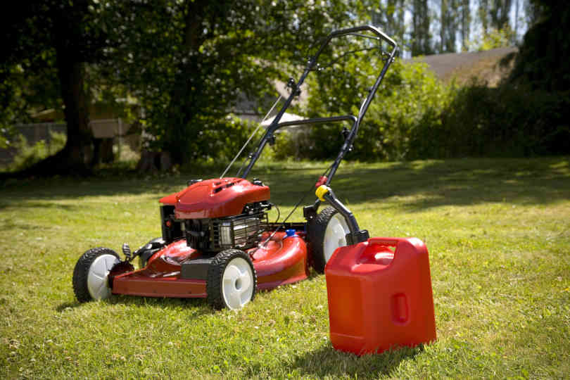 A red lawn mower and gas can in fresh cut grass.