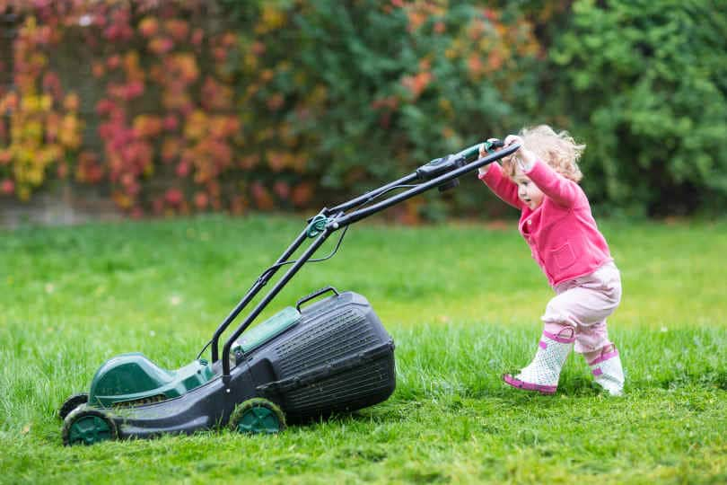 Cute curly baby girl in rain boots playing in a big green lawn with walk behind lawn mower