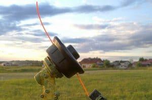 Gasoline grass trimmer professional gardening tool on mown grass