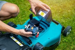 Gardener putting battery into electric cordless lawn mower