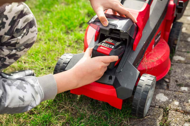 Gardener changes rechargeable battery in riding lawn mower